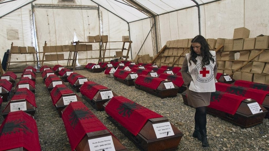 A Kosovo Red Cross volunteer looks at 46 coffins draped with Albanian flags containing the remains of ethnic Albanians killed during the 1998-99 Kosovo war in capital Pristina on Monday, March 24, 2014. The victims were killed in two separate rampages by Serbs forces in western Kosovo just days after NATO began a bombing campaign to stop Serbia's onslaught on separatist ethnic Albanians on March 1999. (AP Photo/Visar Kryeziu)