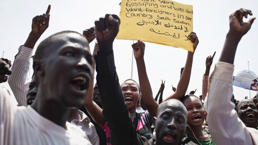 "A group of South Sudanese chant at a demonstration held in support of President Salva Kiir and against ""foreign encroachment"" in Juba, South Sudan Monday, March 10, 2014. Arabic on placard reads ""No foreigners are allowed to intervene"". The rally participants marched through the city on Monday and shouted slogans of support for President Salva Kiir while also denouncing Hilde Johnson, the top U.N. official in the country, accusing Johnson of supplying arms to rebels fighting South Sudan's government. (AP Photo/Mackenzie Knowles-Coursin)"