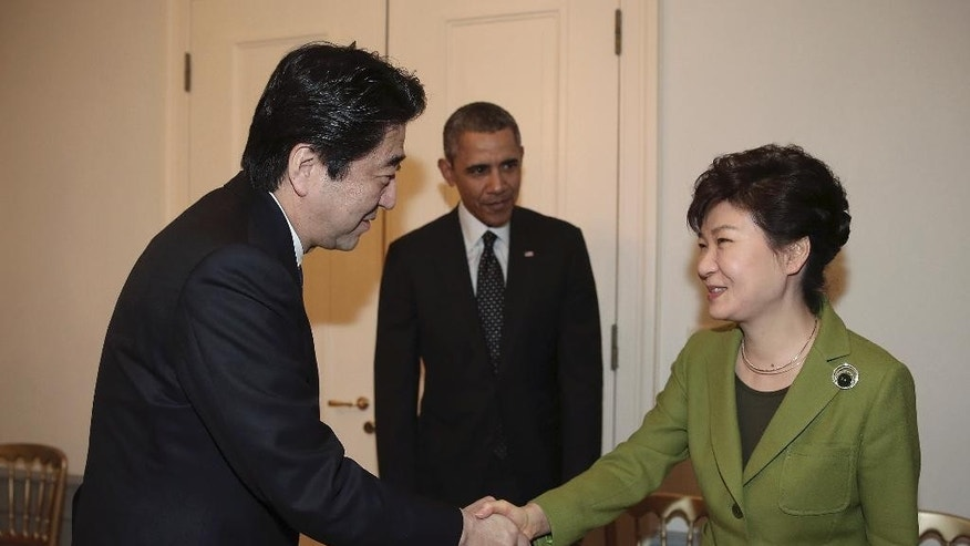 South Korean President Park Geun-hye, right, shakes hands with Japanese Prime Minister Shinzo Abe, left, as U.S. President Barack Obama looks on before their trilateral meeting at the U.S. Ambassador's Residence in the Hague, Netherlands, Tuesday, March 25, 2014. (AP Photo/Yonhap, Do Kwang-hwan)  KOREA OUT