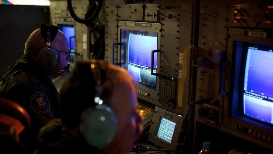"In this Monday, March 24, 2014 photo, crewmen on board an RAAF AP-3C Orion aircraft look at their radar screens whilst searching for missing Malaysia Airlines Flight MH370 over the Indian Ocean. After 17 days of desperation and doubt over the missing Malaysia Airlines jet, Malaysian officials on Monday said an analysis of satellite data points to a ""heartbreaking"" conclusion: Flight 370 met its end in the southern reaches of the Indian Ocean, and none of those aboard survived.  (AP Photo/Richard Wainwright, Pool)"