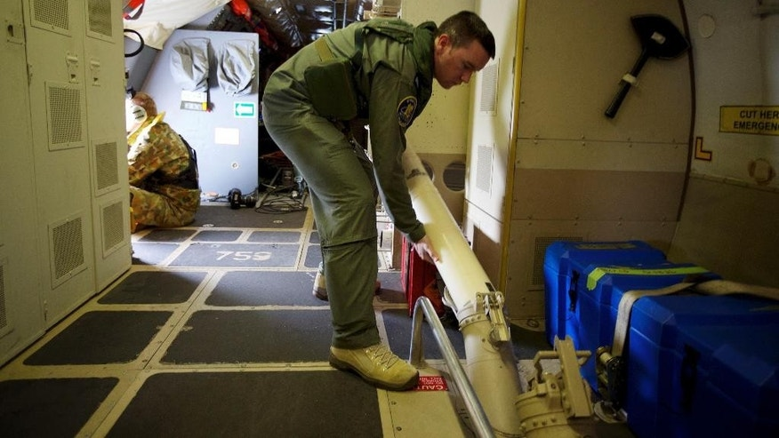 "In this Monday, March 24, 2014 photo, a crewman of an RAAF AP-3C Orion aircraft loads a sonar buoy that will mark the location of any wreckage found whilst searching for missing Malaysia Airlines Flight MH370 over the Indian Ocean. After 17 days of desperation and doubt over the missing Malaysia Airlines jet, Malaysian officials on Monday said an analysis of satellite data points to a ""heartbreaking"" conclusion: Flight 370 met its end in the southern reaches of the Indian Ocean, and none of those aboard survived.  (AP Photo/Richard Wainwright, Pool)"