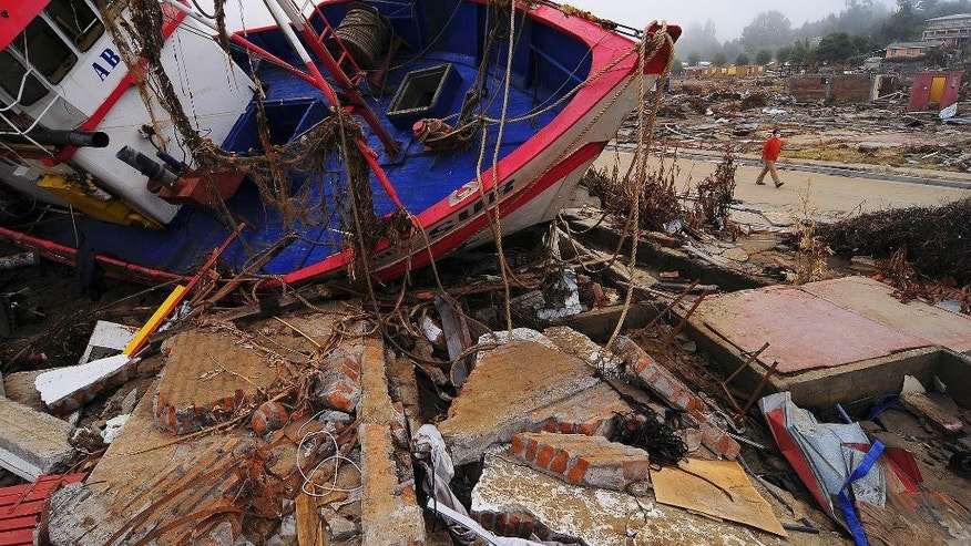FILE - In this March 10, 2010 file photo, a boat sits on the rubble of a house in Dichato, Chile, after magnitude-8.8 quake and ensuing tsunami in central Chile in  Feb. 27, 2010 killed more than 500 people, destroyed 220,000 homes, and washed away docks, riverfronts and seaside resorts. A strong magnitude-6.7 earthquake off Chile's far-northern coast on March 16. 2014, caused more than 100,000 people to briefly evacuate low-lying areas and has been followed by an unsettling string of more than 300 aftershocks. Chile is one of the world's most earthquake-prone countries. (AP Photo/Francisco Negroni, File)
