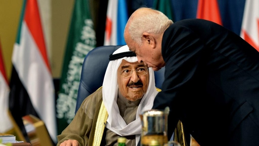 Emir of Kuwait, Sheikh Sabah al-Ahmad al-Sabah, left, speaks with Secretary-General of the League of Arab States, Nabil El Araby, during the opening session of the Arab League Summit in Bayan Palace, Kuwait City, Tuesday, March 25, 2014. Qatar's ruler Sheik Tamim bin Hamad bin Khalifa Al Thani a made thinly veiled criticism of Iraq's Shiite-led government and Egyptian authorities in an address to the opening session of the Arab summit, a move that is likely to add a new layer to tension in the region. (AP Photo/Nasser Waggi)
