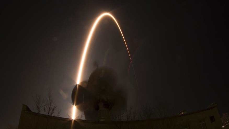 In this photo taken with a fisheye lens and long exposure, the Soyuz-FG rocket booster with Soyuz TMA-12M space ship carrying a new crew to the International Space Station (ISS) blasts off over an antenna at the Russian leased Baikonur cosmodrome, Kazakhstan, Wednesday, March 26, 2014. The Russian rocket carries U.S. astronaut Steven Swanson, Russian cosmonauts Alexander Skvortsov and Oleg Artemyev. (AP Photo/Dmitry Lovetsky)
