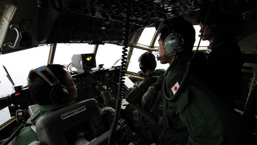 FILE - In this March 21, 2014 file photo, Japanese Air Self-Defense Force's Capt. Junichi Tanoue, left, co-pilot Ryutaro Hamahira, second from left, and engineer Noriyuki Yamanouchi, second from right, scan the ocean aboard a C130 aircraft while it flies over the southern search area in the southeastern Indian Ocean, 200 to 300 kilometers (124 to 186 miles) south of Sumatra, Indonesia. Not one object has been recovered from the missing airliner that Malaysian officials are now convinced plunged into the southern Indian Ocean 17 days ago. Some of the pieces are likely 3,500 meters (11,500 feet) underwater. Others are bobbing in a fickle system of currents that one oceanographer compares to a pinball machine. And by now, they could easily be hundreds of kilometers (miles) away from each other.  (AP Photo/Koji Ueda, File)