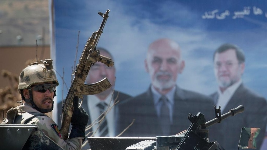 An Afghan special forces soldier takes up position next to an election campaign poster of presidential candidate Ashraf Ghani Ahmadzai, center on the poster, after the Taliban launched an assault with a suicide bomber detonating his vehicle outside an election office in Kabul, Afghanistan, Tuesday, March 25, 2014. Gunmen stormed into the building, trapping dozens of employees inside and killing many people. A candidate for a seat on a provincial council was among those killed, along with an election worker, a civilian and a policeman. (AP Photo/Anja Niedringhaus)