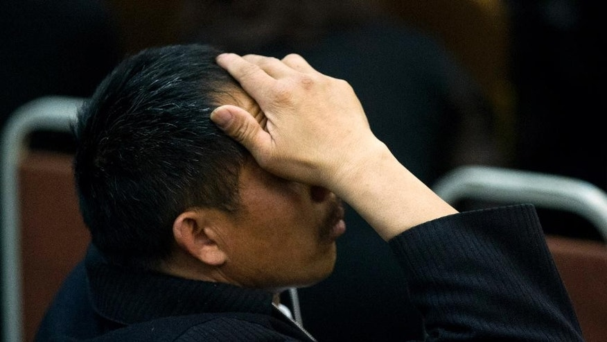 One of the relatives of Chinese passengers on board Malaysia Airlines Flight 370 rubs his head during a briefing meeting given by Malaysian official at a hotel in Beijing, China, Wednesday, March 26, 2014. The search of the missing plane resumed Wednesday after fierce winds and high waves forced crews to take a break Tuesday. A total of 12 planes and five ships from the United States, China, Japan, South Korea, Australia and New Zealand were participating in the search, hoping to find even a single piece of the jet that could offer tangible evidence of a crash and provide clues to find the rest of the wreckage.  (AP Photo/Alexander F. Yuan)