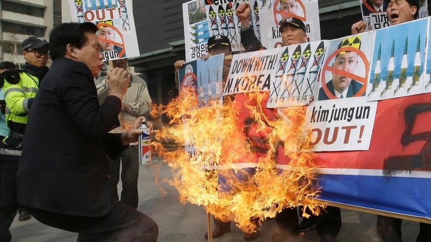 Anti-North Korean protesters burn a North Korean flag and pictures of the North's leader Kim Jong Un during a rally in downtown Seoul, South Korea, Wednesday, March 26, 2014. North Korea test-fired two medium-range ballistic missiles on Wednesday, South Korea and the U.S. said, a defiant challenge to a rare three-way summit of its rivals Seoul, Tokyo and Washington that focused on the North's security threat. (AP Photo/Lee Jin-man)