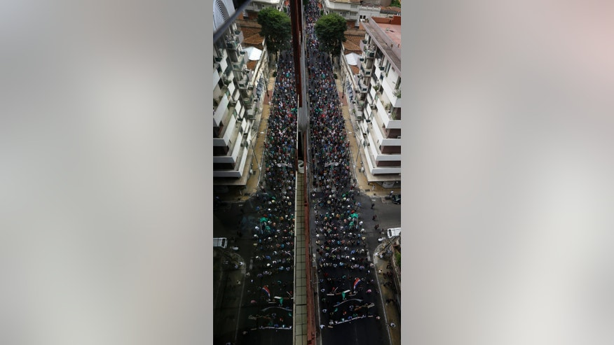 The glass from a balcony, reflects a mirror image of marchers in a general strike, the first in 20 years, in Asuncion, Paraguay, Wednesday, March 26, 2014. Workers, farmers, teachers and students united seeking a variety of demands from the Horacio Cartes government that include price control for basic foods, free, quality education, a raise in minimum wage, agrarian reform and an end to violence against small farmers. (AP Photo/Jorge Saenz)