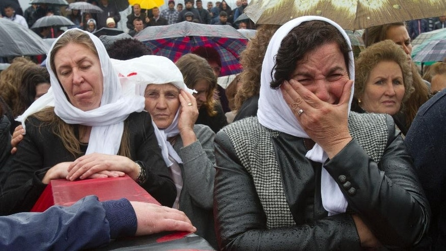 Ethnic Albanian woman weep next to a coffin draped with the Albanian flag containing the remains of her relative killed during the 1998-99 Kosovo war in the town of Mala Krusa during the funeral ceremony of 19 ethnic Albanians on Wednesday, March 26, 2014. The victims were killed in two separate rampages by Serbs forces in town of Suva Reka and Mala Krusa just days after NATO began a bombing campaign to end an onslaught by Serbia on separatist ethnic Albanians. (AP Photo/Visar Kryeziu)