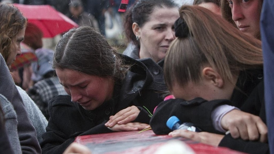 Ethnic Albanian women weep during the funeral ceremony of 19 ethnic Albanians killed during the 1998-99 Kosovo war in the town of Mala Krusa on Wednesday, March 26, 2014. The victims were killed in two separate rampages by Serbs forces in town of Suva Reka and Mala Krusa just days after NATO began a bombing campaign to end an onslaught by Serbia on separatist ethnic Albanians. (AP Photo/Visar Kryeziu)