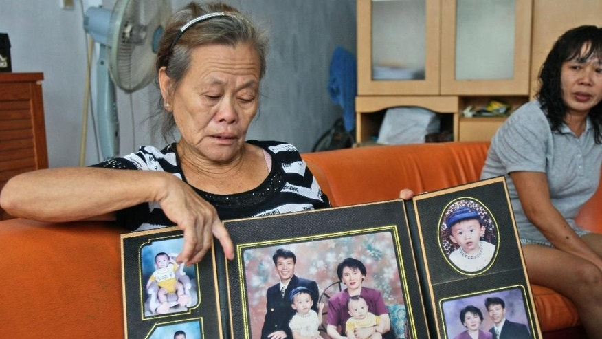 "Suwarni the mother of Sugianto Lo, who was onboard the Malaysia Airlines plane MH370 with his wife Vinny, shows her son's family portraits at her residence in Medan, North Sumatra, Indonesia, Tuesday, March 25, 2014. After 17 days of desperation and doubt over the missing Malaysia Airlines jet, the country's officials said an analysis of satellite data points to a ""heartbreaking"" conclusion: Flight 370 met its end in the southern reaches of the Indian Ocean, and none of those aboard survived. (AP Photo/Binsar Bakkara)"