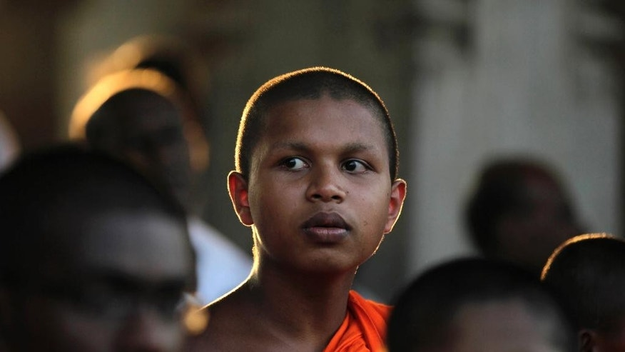 A Sri Lankan Buddhist monk participates in a vigil condemning a U.S. backed resolution against Sri Lanka on alleged war crimes at the U.N. Human Rights Council, in Colombo, Sri Lanka, Tuesday, March 25, 2014. The United Nations human rights body is expected this week to vote on a United-States sponsored resolution over Sri Lanka's failure to investigate alleged war crimes in the final stages of the country's decades-long civil war. (AP Photo/Eranga Jayawardena)