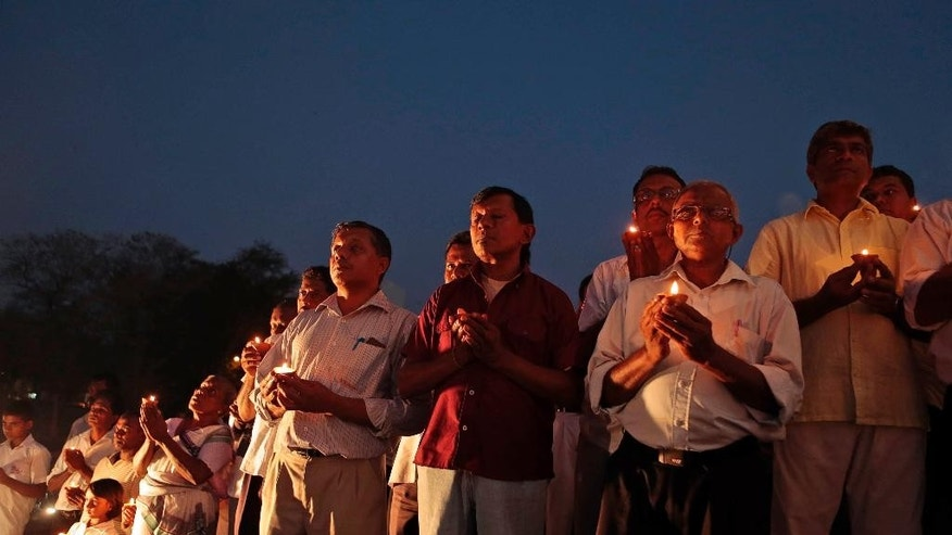 Sri Lankan government supporters hold oil lamps during a vigil condemning a U.S. backed resolution against Sri Lanka on alleged war crimes at the U.N. Human Rights Council, in Colombo, Sri Lanka, Tuesday, March 25, 2014. The United Nations human rights body is expected this week to vote on a United-States sponsored resolution over Sri Lanka's failure to investigate alleged war crimes in the final stages of the country's decades-long civil war. (AP Photo/Eranga Jayawardena)