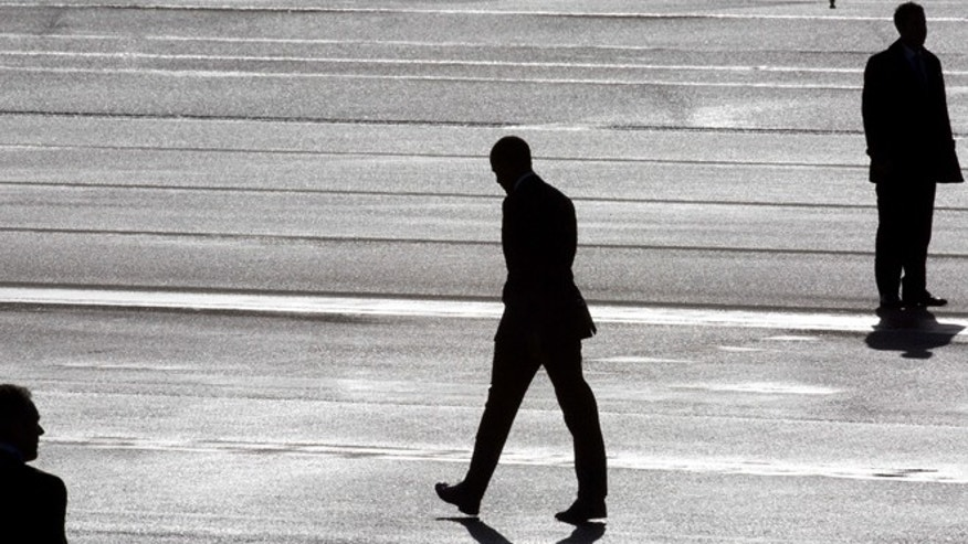 President Barack Obama, center, and two secret service agents are silhouetted as he walks towards Marine One helicopter upon arrival at Schiphol Amsterdam Airport, Netherlands, Monday March 24, 2014. Obama will attend the two-day Nuclear Security Summit in The Hague. (AP Photo/Peter Dejong, POOL)