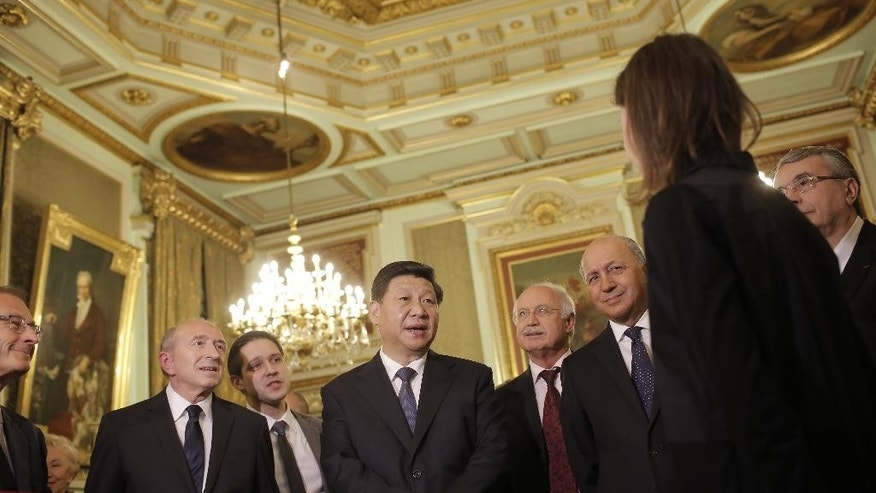 Chinese President Xi Jinping, center, Lyon's mayor Gerard Collomb, left, and French foreign minister Laurent Fabius, second right, listen to a local unidentified businessman before a dinner at the town hall in Lyon, central France, Tuesday, March 25, 2014. Xi Jinping arrived in France for a three-day state visit. (AP Photo/Laurent Cipriani, Pool)