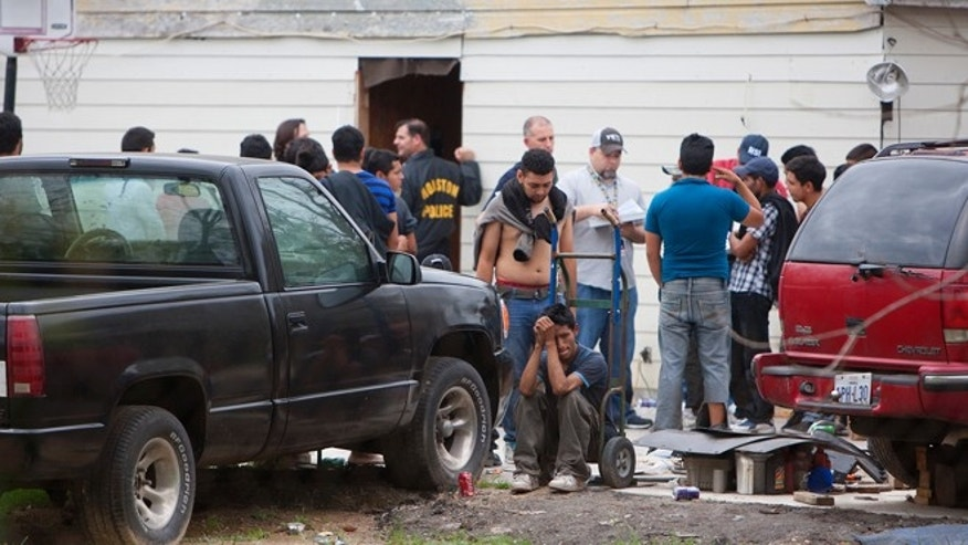 People wait outside a house, Wednesday, March 19, 2014, in southeast Houston. A house overflowing with more than 100 people presumed to be in the United States illegally was uncovered just outside Houston on Wednesday, a police spokesman said. The suspected stash house was found during a search for a 24-year-old woman and her two children that were reported missing by relatives Tuesday after a man failed to meet them, said a spokesman for the Houston Police Department. (AP Photo/Houston Chronicle, Cody Duty)