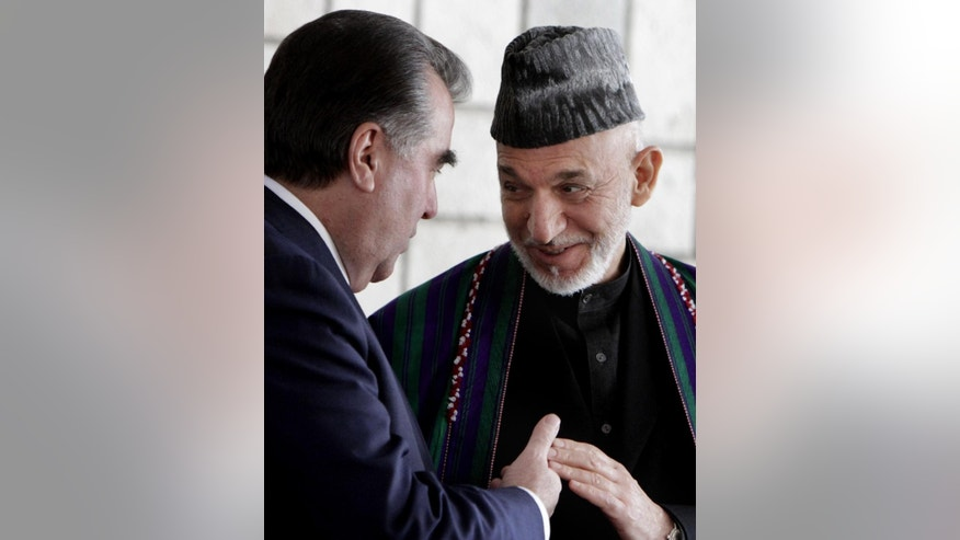 Tajikistan's President Emomali Rakhmon, left, and Afghan President Hamid Karzai, speak during a press conference in Kabul, Afghanistan, Wednesday, March 26, 2014. (AP Photo/S. Sabawoon, Pool)