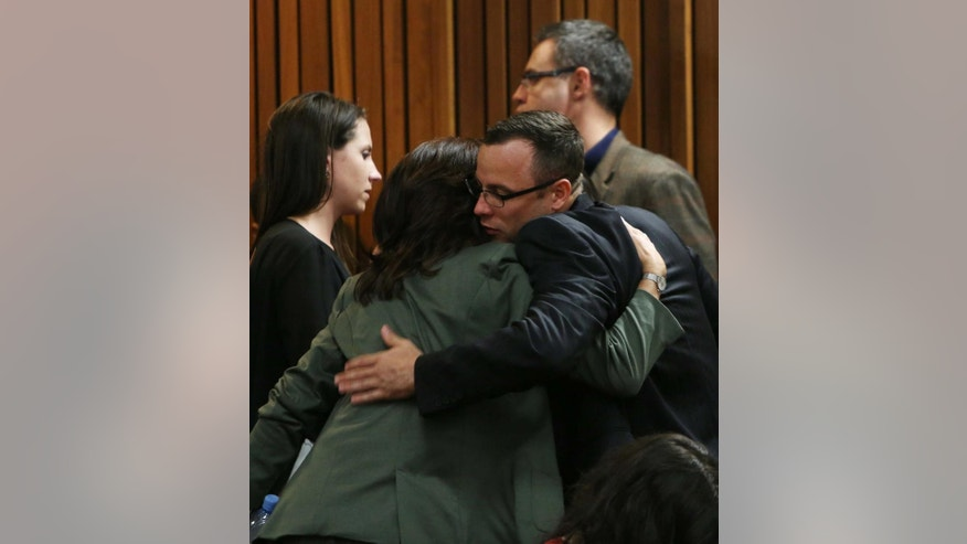 Oscar Pistorius greets and hugs family and friends as the prosecution wraps up its case in Pretoria, South Africa, Tuesday, March 25, 2014. Pistorius is charged with the Valentines Day 2013 shooting death of his girlfriend Reeva Steenkamp. (AP Photo/Esa Alexander, Pool)