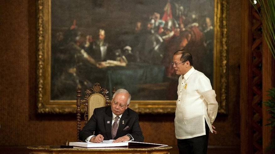 Philippine President Benigno Aquino, right, stands beside Malaysian Prime Minister Najib Razak as he signs the guesst book at Malacanang palace in Manila, Philippines, Thursday, March 27, 2014, before the signing of the Comprehensive Agreement on the Bangsamoro. The Philippine government signed a peace accord with the country's largest Muslim rebel group on Thursday, the culmination of years of negotiations and a significant political achievement for Aquino.  (AP Photo/Noel Celis, Pool)