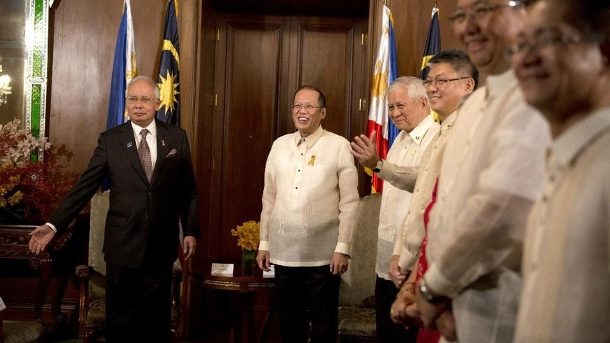 Philippine President Benigno Aquino, center right, welcomes Malaysian Prime Minister Najib Razak, left, during a courtesy call at Malacanang palace in Manila, Thursday, March 27, 2014, before the signing of the Comprehensive Agreement on the Bangsamoro at the Malacanan Palace in Manila on March 27, 2014. The Philippine government signed a peace accord with the country's largest Muslim rebel group on Thursday, the culmination of years of negotiations and a significant political achievement for Aquino.  (AP Photo/Noel Celis, Pool)