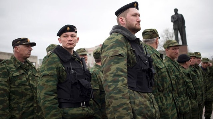 March 27, 2014: Members of the Crimean self defense forces gather for their morning briefing prior to patrolling the city at Soviet Union founder Vladimir Lenin's statue in Simferopol, Crimea. Crimea's government has decided to disband self-defense forces which provided help to the Russian military which have been occupying since late February. (AP Photo/Pavel Golovkin)