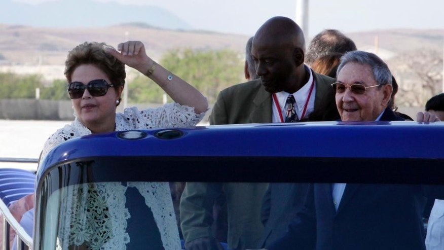 FILE - In this Jan. 27, 2014, file photo, Brazil's President Dilma Rousseff, left, and Cuba's President Raul Castro make a tour by bus after the inauguration ceremony of the first phase of a port overhaul project in Mariel, Cuba. Cuban authorities are on the verge of enacting a new foreign investment law considered one of the most vital building blocks of President Raul Castro's effort to reform the country's struggling economy. Foreign investment in the Communist-run country has lagged behind expectations in recent years, and the shortfall is seen as a major reason for disappointing economic growth. (AP Photo/Ismael Francisco, Cubadebate, File)