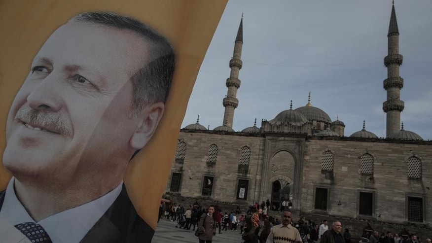 A poster of Turkish Prime Minister Recep Tayyip Erdogan is seen in an election billboard of his Justice and Development Party with a mosque in the background in Istanbul, Turkey, Thursday, March 27, 2014. Erdogan has been ensnared in a corruption scandal that has toppled four Cabinet ministers. He has provoked outrage at home and abroad with an attempt to block Twitter and YouTube. His incessant us-against-them rhetoric and conspiracy theories have alienated allies. Meanwhile, the Turkish Lira has fallen, interest rates are up and the Turkish economy has fallen off a cliff. It all might be enough to oust any leader. But as Turks prepare to vote in local elections Sunday, it's all about Erdogan.(AP Photo/Emrah Gurel)