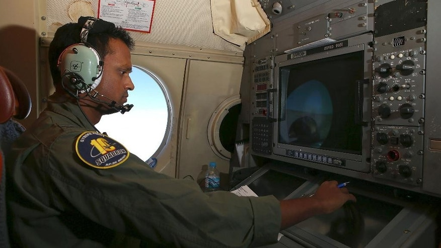 "In this Wednesday, March 26, 2014 photo, Tactical Coordinator Imray Cooray operates from his station on board a Royal Australian Air Force AP-3C Orion during a search for the missing Malaysia Airlines Flight 370 in the southern Indian Ocean. A French satellite scanning the Indian Ocean for remnants of the missing jetliner found a possible plane debris field containing 122 objects, a top Malaysian official said Wednesday, calling it ""the most credible lead that we have."" (AP Photo/Paul Kane, Pool)"