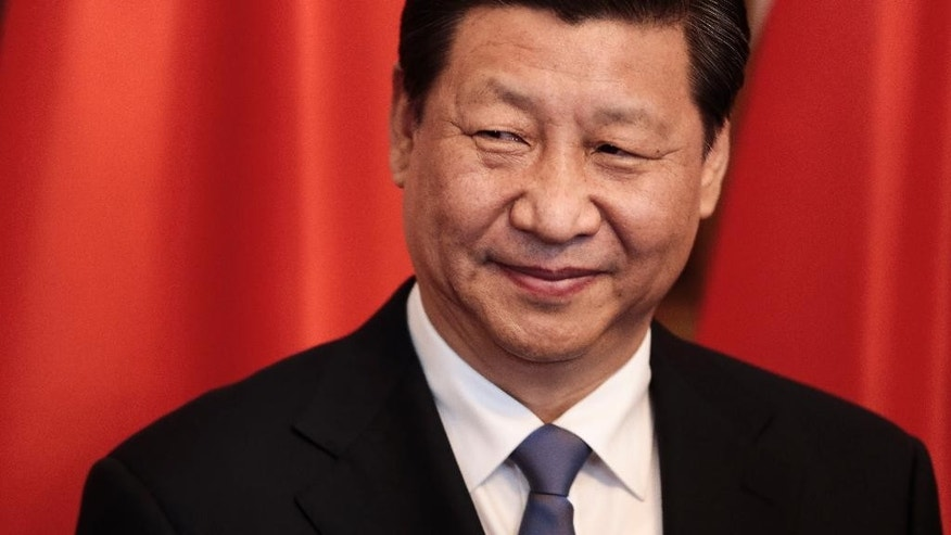 Chinese President Xi Jinping stands in front of a Chinese flag as he welcomes guests for the official lunch during his visit at the German President's resident Bellevue palace in Berlin, GermanyFriday, March 28, 2014. (AP Photo/Markus Schreiber)