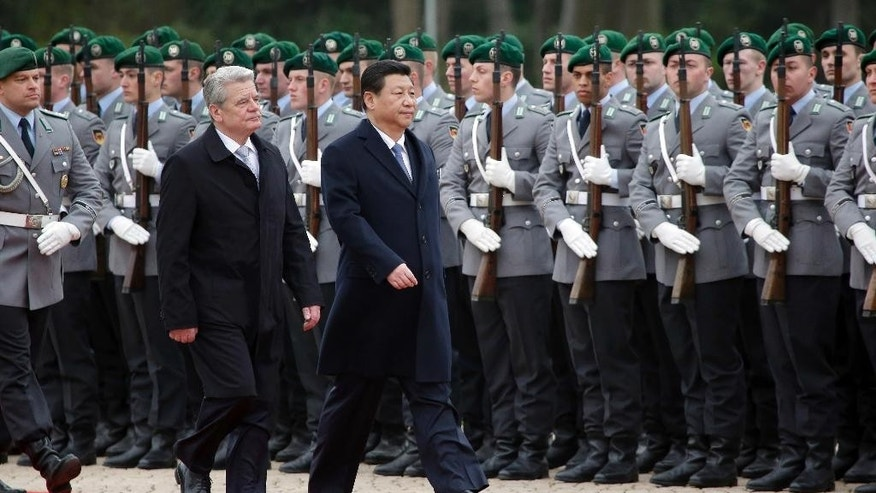 German President Joachim Gauck, left, welcomes the President of China Xi Jinping, right, with military honors for a meeting at the Bellevue Palace in Berlin, Germany, Friday, March 28, 2014. (AP Photo/Michael Sohn)