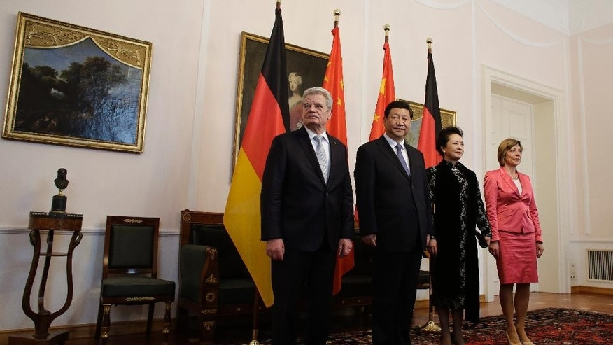 German President Joachim Gauck, left, his partner Daniela Schadt, right, and Chinese President Xi Jinping, 2. from left, and his wife Peng Liyuan, 2. from right, arrive to welcomes guests prior to the official lunch during their visit at German President's resident Bellevue palace in Berlin, Germany, Thursday, March 28, 2013. (AP Photo/Markus Schreiber)