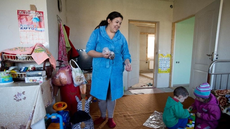 In this photo taken Thursday, March 27, 2014 Crimea's Tatar Liliya Resulova, 24, smiles as her son, Emir, 2, center, plays with Diana Setumirova, 4, right, inside of their building at recent squatter settlement  in Lozovoye-2 not far from Simferopol, Crimea. On Saturday the Crimean Tatar Qurultay, a religious congress will determine whether the Tatars will accept Russian citizenship and the political system that comes with it, or remain Ukrainian citizens on Russian soil. (AP Photo/Pavel Golovkin)