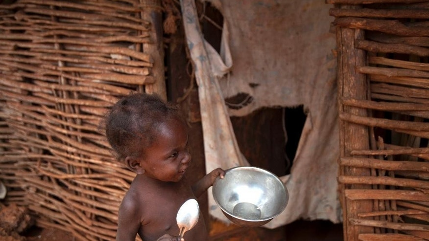 "In this Tuesday, March 25, 2014 photo, with spoon and bowl in hand, 2-year-old Rosemika Beltinor toddles on the perimeters of her home in search of food, in Bombardopolis, in northwest Haiti. ""The rain isn't falling. I can't feed my family,"" said Rosemika's father, Jean-Romain Beltinor. ""Sometimes you spend a couple of days without food.""  (AP Photo/Dieu Nalio Chery)"