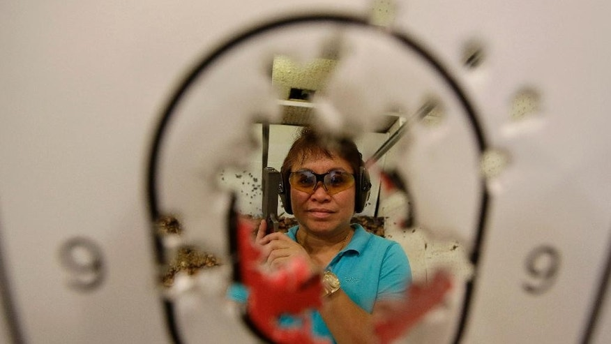 "In this Feb. 9, 2014 photo, Bureau of Internal Revenue Commissioner Kim Henares poses with her score following target practice in a firing range at suburban Mandaluyong city, east of Manila, Philippines. The 53-year-old straight-talking chief has shifted her agency into ""law enforcement mode"" with an aggressive anti-tax evasion campaign to catch cheats and raise collections. Henares is a lawyer and accountant whose hobbies include weekly trips to the firing range where she shoots off automatic pistols and assault rifles. Shooting has become one of her favorite pastimes since she was appointed in July 2010 by President Benigno Aquino III, a gun aficionado who introduced her to the sport. (AP Photo/Bullit Marquez)"