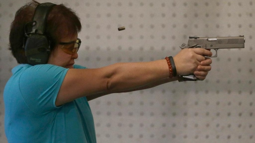"In this Feb. 9, 2014 photo, Bureau of Internal Revenue Commissioner Kim Henares fires her pistol during target practice in a firing range at suburban Mandaluyong city, east of Manila, Philippines. The 53-year-old straight-talking chief has shifted her agency into ""law enforcement mode"" with an aggressive anti-tax evasion campaign to catch cheats and raise collections. Henares is a lawyer and accountant whose hobbies include weekly trips to the firing range where she shoots off automatic pistols and assault rifles. Shooting has become one of her favorite pastimes since she was appointed in July 2010 by President Benigno Aquino III, a gun aficionado who introduced her to the sport. (AP Photo/Bullit Marquez)"