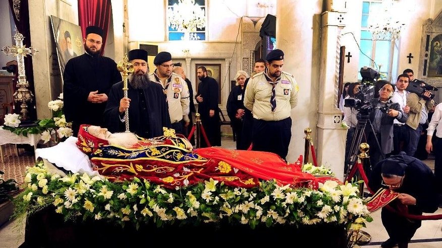In this photo taken on Thursday March 27, 2014 and released by the Syrian official news agency SANA, Syrian clergymen pay their respects to the lifeless body of Patriarch of Syriac Orthodox Church Ignatius Zakka Iwas, during a mass service at St. George's Cathedral, in Damascus, Syria. The Patriarch of Syriac Orthodox Church, who had led one of the world's oldest Christian sects was buried in a Christian village near Damascus on Friday after an elaborate memorial service in the Syrian capital's cathedral. Iwas, a native of Iraq and a vocal proponent of Christian-Muslim coexistence has lived in Damascus since he was enthroned as patriarch in 1980. He died a week ago in a hospital in Germany last week at 80. (AP Photo/SANA)