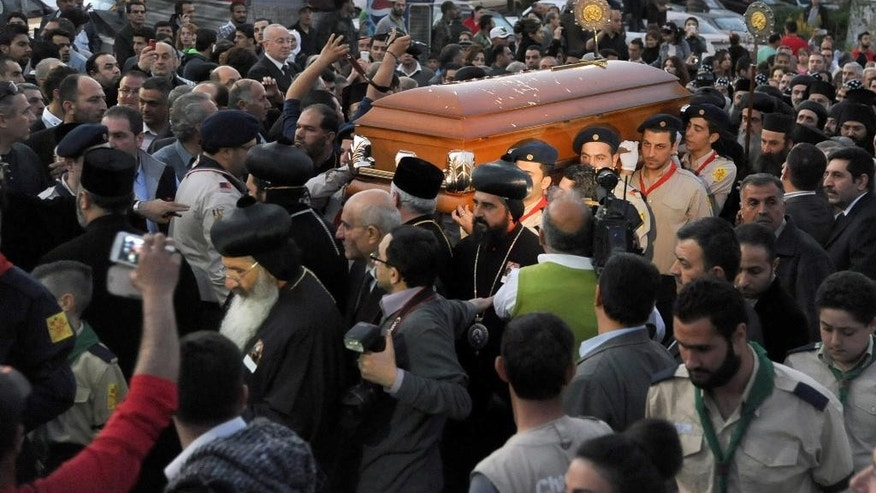 In this photo taken on Thursday March 27, 2014 and released by the Syrian official news agency SANA, Syrian mourners carry the coffin of Patriarch of Syriac Orthodox Church Ignatius Zakka Iwas, as they arrive at St. George's Cathedral, in Damascus, Syria. The Patriarch of Syriac Orthodox Church, who had led one of the world's oldest Christian sects was buried in a Christian village near Damascus on Friday after an elaborate memorial service in the Syrian capital's cathedral. Iwas, a native of Iraq and a vocal proponent of Christian-Muslim coexistence has lived in Damascus since he was enthroned as patriarch in 1980. He died a week ago in a hospital in Germany last week at 80. (AP Photo/SANA)