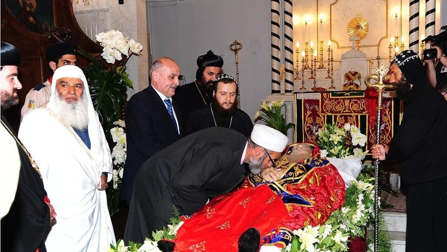 In this photo taken on Thursday March 27, 2014 and released by the Syrian official news agency SANA, a Syrian Muslim sheik, center, kisses the hand of the lifeless body of Patriarch of Syriac Orthodox Church Ignatius Zakka Iwas, during a mass service at St. George's Cathedral, in Damascus, Syria. The Patriarch of Syriac Orthodox Church, who had led one of the world's oldest Christian sects was buried in a Christian village near Damascus on Friday after an elaborate memorial service in the Syrian capital's cathedral. Iwas, a native of Iraq and a vocal proponent of Christian-Muslim coexistence has lived in Damascus since he was enthroned as patriarch in 1980. He died a week ago in a hospital in Germany last week at 80. (AP Photo/SANA)