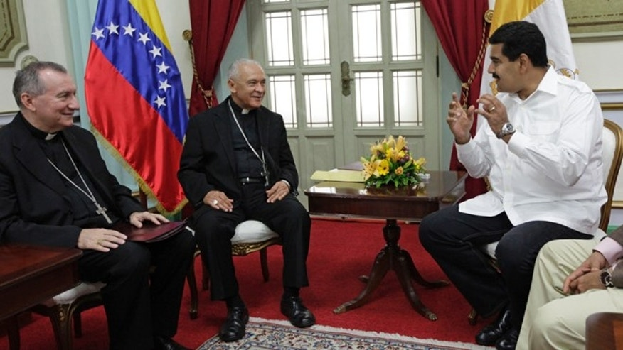 June 14, 2013: In thisphoto, Venezuela's President Nicolas Maduro, right, meets with Venezuela's Archbishop Diego Rafael Padron Sanchez, left and Italian Pietro Parolin, Holy See's representative in Venezuela, at Miraflores presidential palace in Caracas, Venezuela.