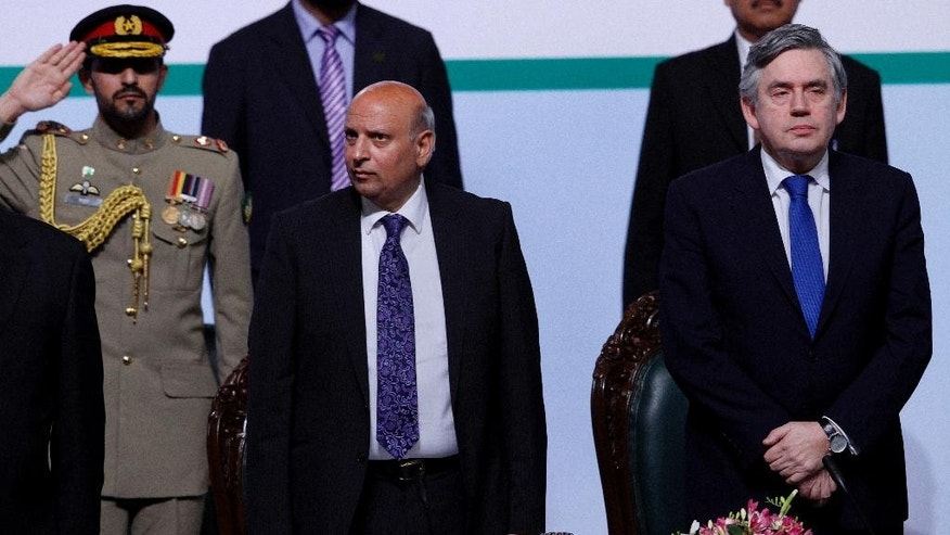 Former British Prime Minister and U.N. special envoy for Global Education, Gordon Brown, right, and Governor of Pakistani Punjab province Chaudary Muhammad Sarwar, center, stand for the national anthem during an education conference in Islamabad, Pakistan, Saturday, March 29, 2014. Brown said the world community will give about one billion dollars to Pakistan during the next three to four years to help its efforts aimed at providing education to millions of boys and girls who are missing education. (AP Photo/Anjum Naveed)
