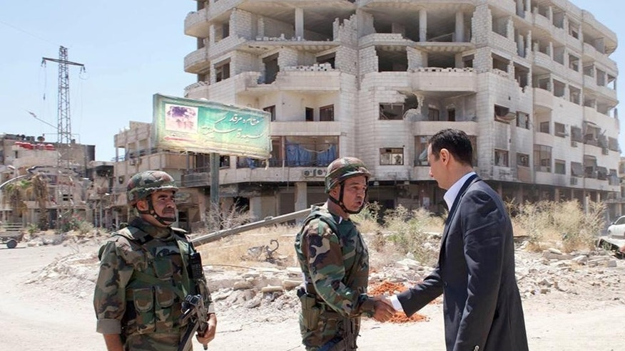 FILE - This Aug. 1, 2013 file photo posted on the official Facebook page of the Syrian Presidency shows Syrian President Bashar Assad shaking hands with a soldier during Syrian Arab Army day in Darya, Syria. As the Syrian conflict entered its forth year this month and large parts of the country are either destroyed or under opposition control, Syrian officials say the presidential elections will be held on time later this year.The opposition rejects such a move saying after the death of more than 140,000 people and millions turned to refugees or displaced, Assad should step down rather than run again. (AP Photo/Syrian Presidency via Facebook, File)