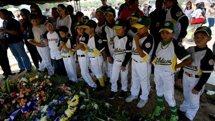 "In this photo taken on Friday, March 14, 2014. Boys that play in a minor league baseball team ""Atleticos de Crimon"" mourn their coach, Guillermo Sanchez after his funeral grave in  in Valencia, Venezuela. The people of the poor district of La Isabelica were made to pay for taking to the streets in anti-government protests. More than a dozen masked men on motorcycles roared through, shooting up a barricade and killing a university student and a 42-year-old man painting his house. (AP Photo/Fernando Llano)"