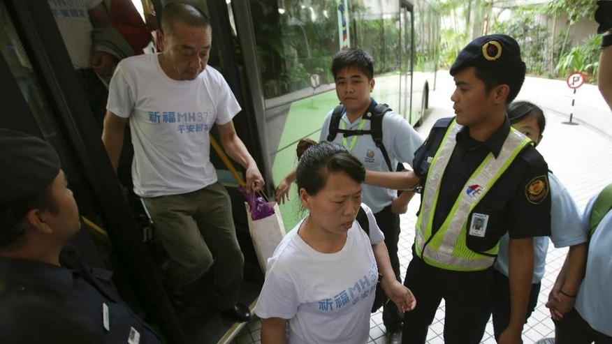 A new batch of Chinese relatives of passengers on board the missing Malaysia Airlines Flight 370 arrive at a hotel in Subang Jaya, Malaysia, Sunday March 30, 2014. A new batch of relatives from China arrived Sunday to seek answers from Malaysia's government as to what happened to their loved ones on board the missing Malaysian jetliner. (AP Photo/Aaron Favila)