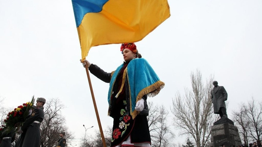 FILE - In this Sunday, March 9, 2014 file photo a young Ukrainian woman holds a Ukrainian flag during celebrations of the 200th birthday anniversary of Ukrainian poet Taras Shevchenko in the Black Sea port of Odessa, Ukraine. The monument to the poet is in the background. Ukraine, a land the size of France with a population of 46 million, has historically been a massive prize in the heart of Europe. The site of the ancient Slavic state, the Kievan Rus, it was the regional cradle of Orthodox Christianity. Over centuries, parts of Ukraine have belonged to Poland, the Austro-Hungarian Empire, Russia and the Soviet Union. (AP Photo/ Sergei Poliakov, File)