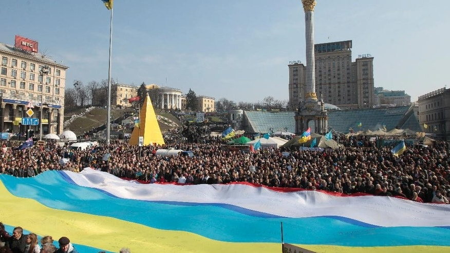 FILE In this Sunday, March 23, 2014 file photo people display Ukrainian, Crimean and Crimean Tatar flags,  during rally in support of Ukraine's territorial integrity, in Kiev's Independence Square, Ukraine. Ukraine, a land the size of France with a population of 46 million, has historically been a massive prize in the heart of Europe. The site of the ancient Slavic state, the Kievan Rus, it was the regional cradle of Orthodox Christianity. Over centuries, parts of Ukraine have belonged to Poland, the Austro-Hungarian Empire, Russia and the Soviet Union. (AP Photo/Sergei Chuzavkov, File)