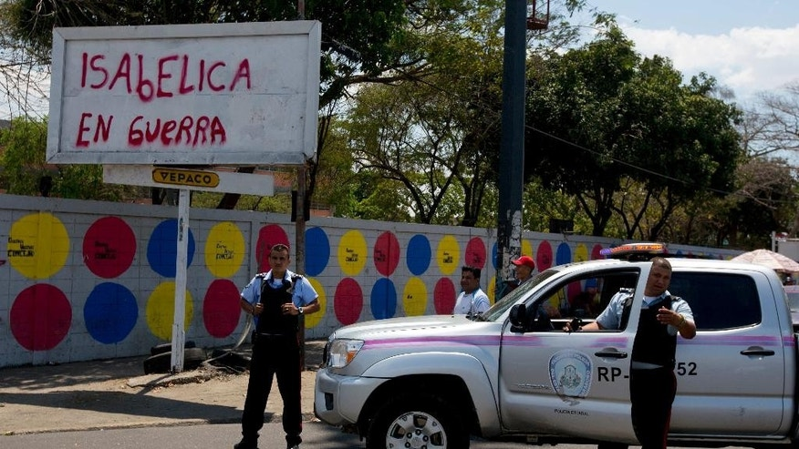 "In this photo taken on Saturday, March 15, 2014. Carabobo's State police officers stand next to graffiti that reads in Spanish ""Isabelica in war""  during a opposition protest at Isabelica neighborhood outside Valencia , Venezuela. The people of the poor district of La Isabelica were made to pay for taking to the streets in anti-government protests. More than a dozen masked men on motorcycles roared through, shooting up a barricade and killing a university student and a 42-year-old man painting his house. (AP Photo/Fernando Llano)"