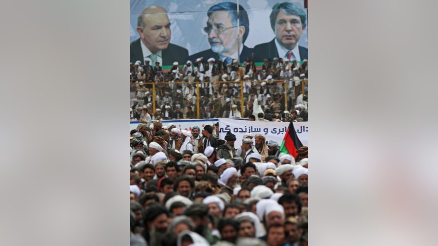 Supporters of Afghanistan's presidential candidate and former foreign minister Zalmai Rassoul, listen to his speech during a campaign rally in Herat, Afghanistan, Sunday, March 30, 2014. The poster shows a photo of Zalmai Rassoul, center, and two brothers of Afghan president Hamid Karzai's photos. Eight Afghan presidential candidates are campaigning for the third presidential election. Elections will take place on April 5, 2014. (AP Photo/Massoud Hossaini)