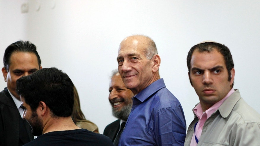 July 10, 2012: Former Israeli Prime Minister Ehud Olmert stands next to lawyers at Jerusalem's District Court following a verdict hearing in his trial.