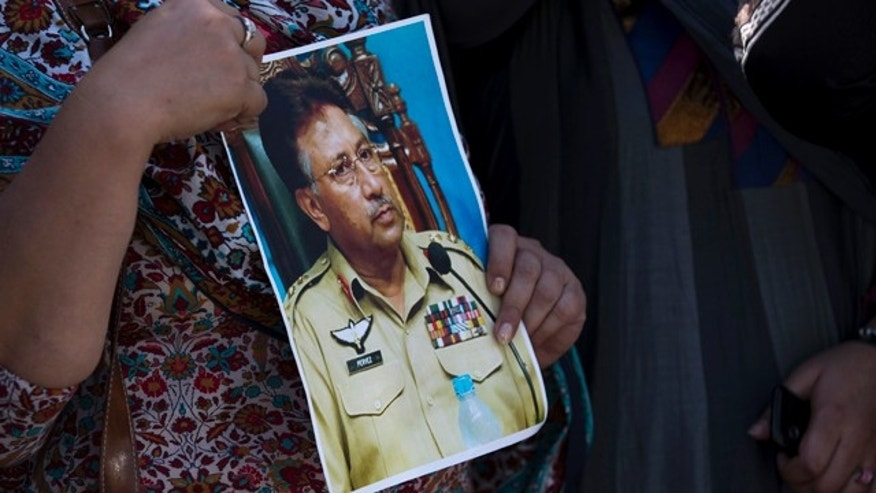 March 31, 2014: A supporter of former Pakistani President Pervez Musharraf holds a photo of him outside the special court in Islamabad. A special court Monday indicted former military ruler Musharraf on five counts of high treason, marking a sharp blow to the country's powerful military. (AP Photo/B.K. Bangash)